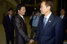 Kim Kiwoong, right, the head of South Korea's working-level delegation, shakes hands with his North Korean counterpart Park Chol Su after their meeting at Kaesong Industrial District Management Committee in Kaesong, North Korea, July 25, 2013.