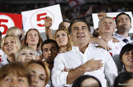 Georgia's President and leader of the ruling United National Movement party Mikheil Saakashvili gestures during the national anthem with his supporters during an election rally at a stadium in Tbilisi September 28, 2012. REUTERS/David Mdzinarishvili