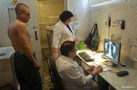 A man (L) is x-rayed to detect tuberculosis during a medical examination, organized by the Belarusian Red Cross society, in Minsk, Jan. 29, 2013.