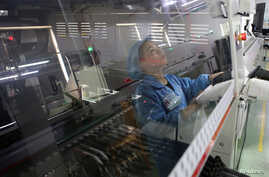 An employee working on the production line of an electronics factory is seen reflected on an equipment, in Jiaxing, Zhejiang province, China, April 2, 2019.