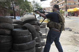 A Sunni gunman takes his position behind a tire barrier as he fires his weapon during clashes on Syria Street which divided the areas between Sunnis and Alawites, in the northern port city of Tripoli, Lebanon, Sunday May 13, 2012.