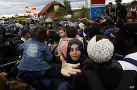 Refugees crowd in front of a line of police officers to cross the border from Croatia to the Slovenian village Rigonce at the border station in Harmica, Croatia, Sunday, Sept. 20, 2015.