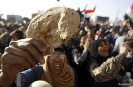 An Egyptian holds a piece of bread to protest against the high prices of goods in Tahrir square in Cairo, February 8, 2013.