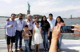 Luis Mendez Chanes, third left, poses with his daughter Marta Mendez, fourth left, as they reunite after 24 years in front of the Statue of Liberty aboard the Bateaux New York boat, July 5, 2017, in New York.