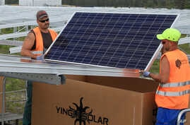 FILE - Workers install solar panels at the Constantine photovoltaic power station in Cestas, near Bordeaux, southwestern France.