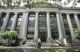 FILE - In this Aug. 1, 2005, image, a bicyclist walks by Harvard University's Langdell Hall, which includes Harvard Law School's library, in Cambridge, Mass. Following an October 2015 talk at Harvard Law School organized by students in the group Just