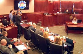 In this image taken from video, accused Colorado theater shooter James Holmes, standing on the far left, listens as the verdict is read during his trial, in Centennial, Colorado, July 16, 2015.