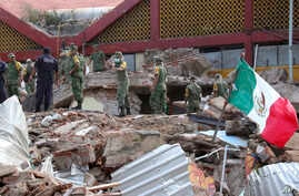 Soldiers remove debris from a partly collapsed municipal building felled by a massive earthquake in Juchitan, Oaxaca state, Mexico, Sept. 8, 2017.