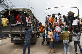 Cambodian workers ride on military trucks as they prepare to cross the Thai-Cambodia border at Aranyaprathet in Sa Kaew, June 15, 2014.