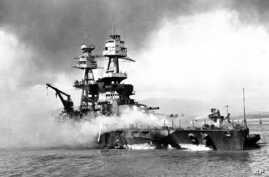 FILE - In this file image provided by the U.S. Navy, crewmen of the USS Nevada fight flames on the battleship, battered in the Japanese aerial attack on Pearl Harbor on Dec. 7, 1941.