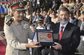 Egypt's new President Mohamed Morsi (R) poses with a gift from Field Marshal Mohamed Tantawi (L), head of Egypt's ruling Supreme Council of the Armed Forces (SCAF), during a ceremony where the military handed over power to Morsi at a military base in