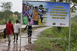 FILE - People walk past a billboard warning residents to stop the stigmatization of Ebola survivors, in Kenema, eastern Sierra Leone, August 12, 2015.