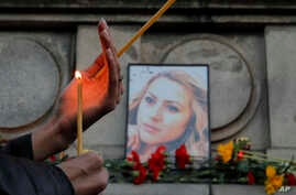 A woman holds a candle next to a portrait of slain television reporter Viktoria Marinova during a vigil at the Liberty Monument in Ruse, Bulgaria, Oct. 8, 2018.