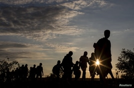 Migrants walk along rail tracks as they arrive at a collection point in the village of Roszke, Hungary, Sept. 8, 2015, after crossing the border from Serbia.