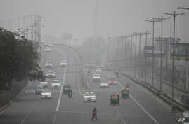An Indian woman crosses a road as vehicles move through morning smog on the last day of a two-week experiment to reduce the number of cars to fight pollution  in New Delhi, Jan. 15, 2016.