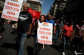 """Members of the communist-affiliated PAME take part in a demonstration marking a general strike against against planned austerity measures in Athens, May 30, 2018. The placards read """"No house to the hands of bankers."""""""