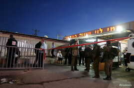 Israeli troops gather near a supermarket that was the scene of a stabbing near the West Bank city of Ramallah, Feb. 18, 2016.