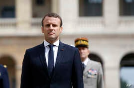 France's President Emmanuel Macron observes the French Flag, during a military ceremony, at the Hotel des Invalides, in Paris, June 30, 2017.