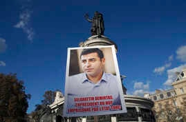 Kurdish demonstrators hold a portrait of pro-Kurdish Peoples' Democratic Party (HDP) leader Selahattin Demirtas during a rally to protest against Turkish President Recep Tayyip Erdogan, at Republique Square in Paris, France, Nov. 5, 2016.