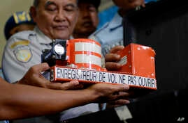 Head of Indonesian National Transportation Safety Committee Tatang Kurniadi, center, shows the newly recovered Cockpit Voice Recorder from the ill-fated AirAsia Flight 8501 during a press conference in Pangkalan Bun, Central Borneo, Indonesia, Tuesda...