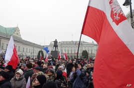 Protesters attend an anti-government demonstration, in Warsaw, Poland, Saturday, Dec. 17, 2016.