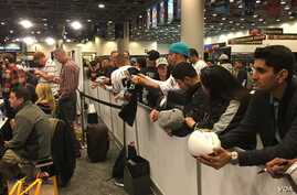 Fans watch the action on Radio Row for Super Bowl 50, at the Moscone Convention Center in San Francisco, Feb. 5, 2016. (P. Brewer/VOA)