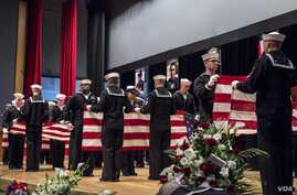 Sailors fold seven American flags during a memorial ceremony in Yokosuka, Japan, June 27, 2017, to honor the seven sailors assigned to the destroyer USS Fitzgerald who were killed in a collision at sea.