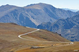 Cars drive Trail Ridge Road, which takes visitors through Rocky Mountain National Park's alpine tundra at elevations of over 3,600 meters.