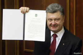 Ukraine's President Petro Poroshenko shows a signed landmark association agreement with the European Union during a session of the parliament in Kyiv, Sept. 16, 2014.