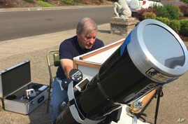 Amateur astronomer Mike Conley practices, Aug. 3, 2017, with the telescope he will use to document the Aug. 21 total solar eclipse, at his home in Salem, Oregon.
