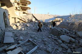 Residents inspect damage after airstrikes by pro-Syrian government forces in Anadan city, about 10 kilometers away from the towns of Nubul and Zahraa, Northern Aleppo countryside, Syri, Feb. 3, 2016.