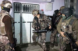Turkish anti-terrorism police break a door during an operation to arrest people over alleged links to the Islamic State group, in Adiyaman, southeastern Turkey, Feb. 5, 2017.