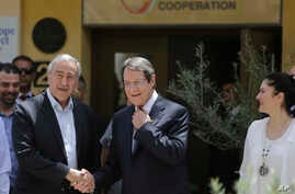 Cyprus' President Nicos Anasatsiades, right, and Turkish Cypriot leader Mustafa Akinci shake hands before they join the Greek and Turkish Cypriots children, inside the U.N. controlled buffer zone at Ledras palace crossing point in divided capital Nic