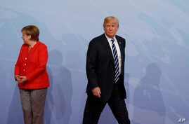 FILE - U.S. President Donald Trump walks off after being greeted by German Chancellor Angela Merkel after arriving at the G20 Summit in Hamburg, Germany, July 7, 2017.