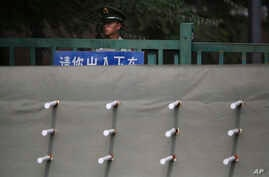 FILE - A Chinese paramilitary policeman stands watch behind a barrier leading to a side road outside the Japanese Embassy in Beijing, Sept. 30, 2015.