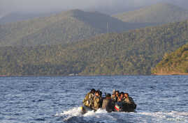 Members of the Philippine marines are transported on a rubber boat from a patrol ship after conducting a mission on the disputed Second Thomas Shoal, part of the Spratly Islands in the South China Sea, as they make their way to a naval forces camp in