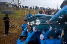 In this Sept. 29, 2017, photo, police lift the coffin of fellow officer Luis Angel Gonzalez Lorenzo, killed during the passage of Hurricane Maria when he tried to cross a river in his car, during his funeral at the cemetery in Aguada, Puerto Rico.