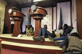 Journalists are seen on the podium following sounds of gunshots before a news conference by South Sudan President Salva Kiir, First Vice President Riek Machar and other government officials inside the Presidential State House in Juba, South Sudan, Ju...
