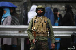 A policeman stands guard outside a polling station in Kabul as Afghans wanting to vote queue outside before it opens April 5, 2014.