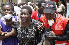 Red Cross staff console a woman after she viewed the body of a relative killed in Thursday's al-Shabab attack at a university in Garissa, northeastern Kenya, at the Chiromo funeral home in Nairobi, Kenya, April 7, 2015.