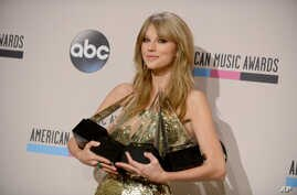 "Taylor Swift poses backstage with the awards for favorite album - country for ""Red"", favorite female artist - pop/rock, favorite female artist - country, and artist of the year at the American Music Awards, Nov. 24, 2013,"