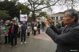 Nguyen Quang A films an anti-China protest in Hanoi, Vietnam, Feb. 17, 2016.