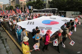 People carry a huge South Korean national flag during a rally to mark the 67th anniversary of the Korean War in Seoul, South Korea, June 25, 2017.