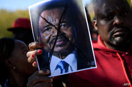 People protest Cameroon's President Paul Biya on Pennsylvania Avenue near the White House, Oct. 22, 2018 in Washington. On Saturday protesters marched and sang on the streets in Douala and other cities.