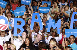Supporters hold signs as U.S. President Barack Obama speaks during a campaign event at Canyon Springs High School in Las Vegas, Nevada, August 22, 2012.