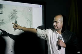 Ernesto Montenegro, director of the Colombian Institute of Anthropology and History of Colombia, talks to reporters while he shows a picture of remains of the galleon San Jose in Cartagena, Colombia, Dec.5, 2015.