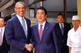 Former U.S. President Barack Obama, left, and Japanese Prime Minister Shinzo Abe pose for photographers in front of Kyubey, a Japanese sushi restaurant, at Ginza shopping district In Tokyo, March 25, 2018.
