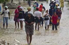Residents leave flooded homes in a low lying area affected by Tropical Storm Isaac in Port-au-Prince, Haiti Aug. 25, 2012  (UN photo)