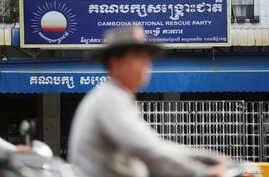 FILE - A man rides a motorcycle past the Cambodia National Rescue Party (CNRP) headquarters in Phnom Penh, Nov. 17, 2017.