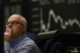 A trader works in front of the German share price index DAX board, at the stock exchange in Frankfurt, Nov. 4, 2015. Frankfurt's DAX index underperformed peers, dragged down by an 8 percent fall in Volkswagen shares.